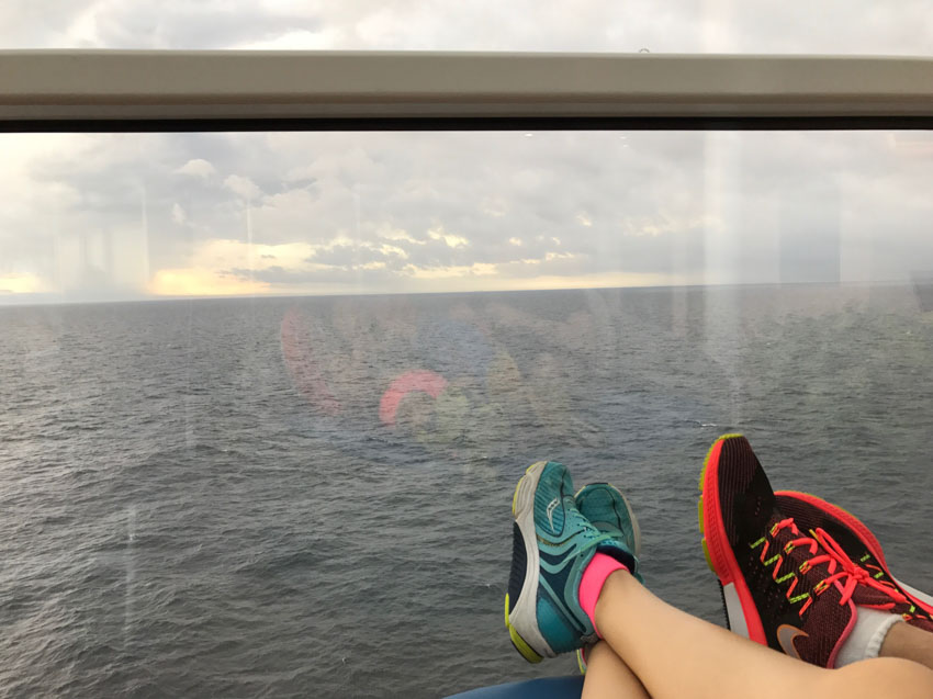 My feet and Nick's feet with our running shoes on, outstretched with the ocean in the background