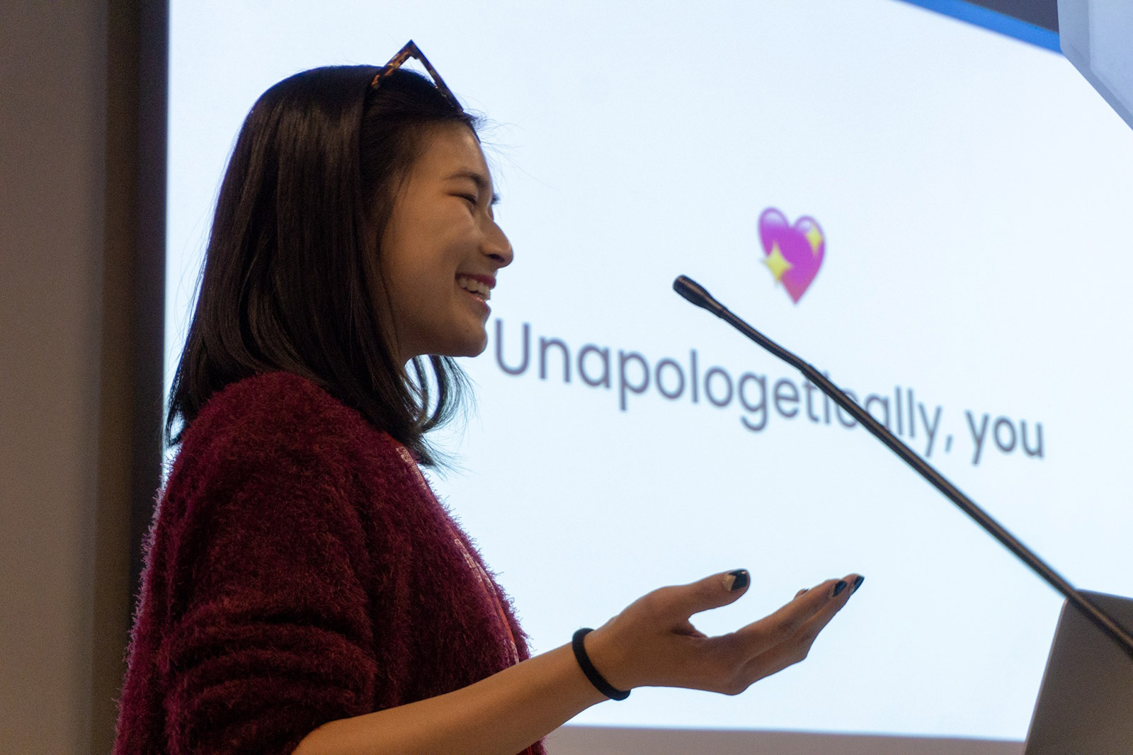 """A woman with her palm upturned, in front of a screen reading """"Unapologetically, you"""""""
