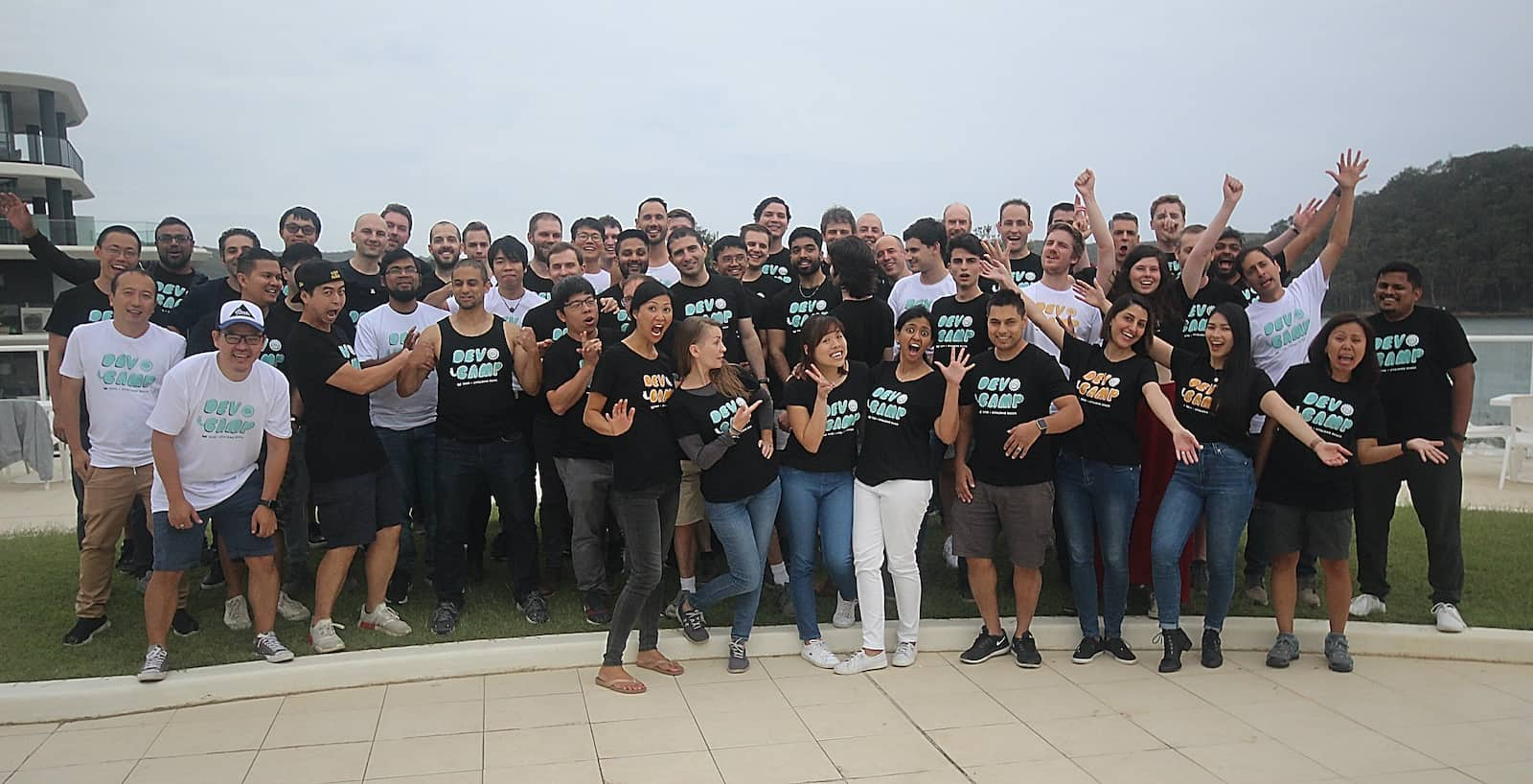 "A group of people wearing shirts with matching bubble text reading ""Devcamp"", some people with their hands in the air. The sea can be seen behind them"