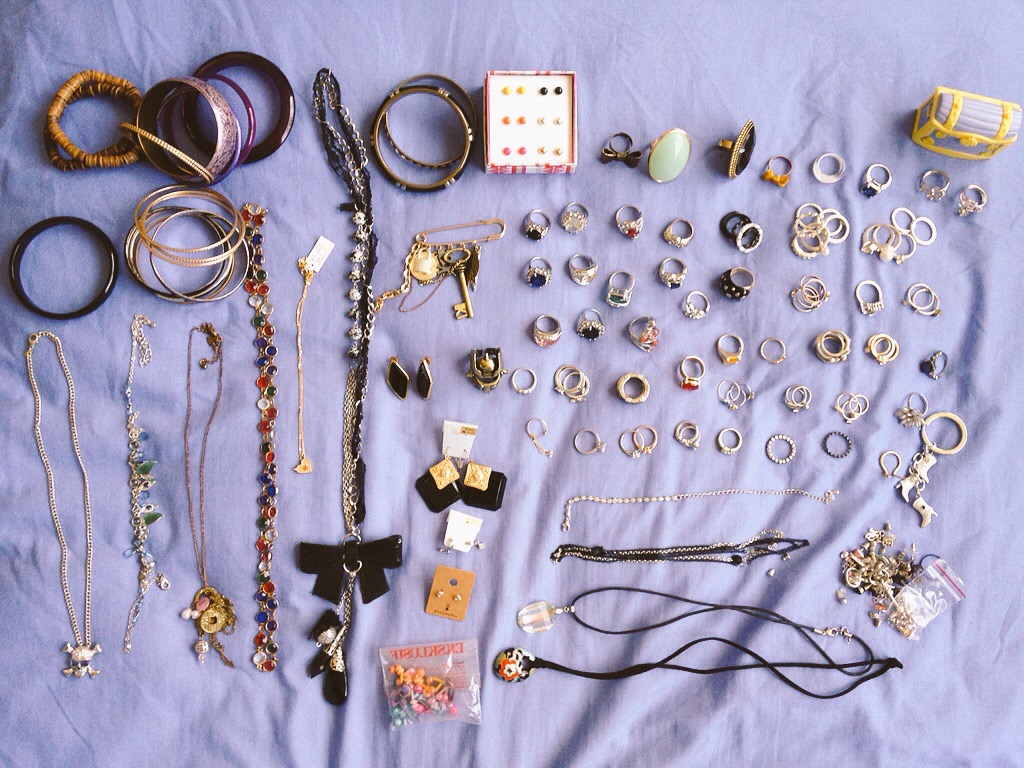 An assortment of necklaces, bangles and rings laid out on a light purple bedspread