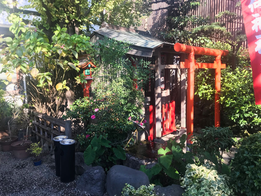 A Japanese shrine with an orange torii gate, a small water feature, a small wooden hut with an awning, and a lot of green leafy trees
