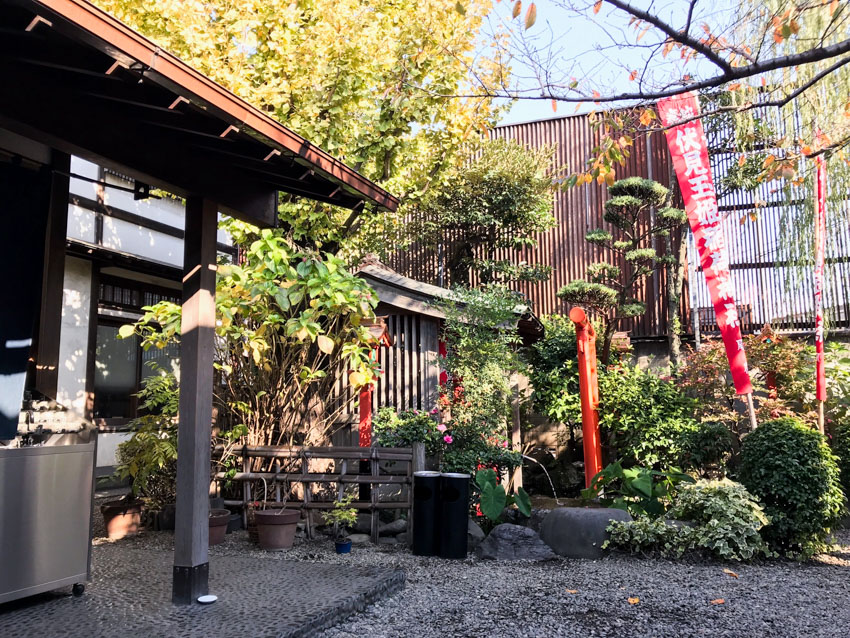 A garden area with small grey stones lining the ground, tall and thin red flags with white Japanese characters on them, plenty of small green plants and trees, some concealing a small hut. In the foreground is the awning of a building.