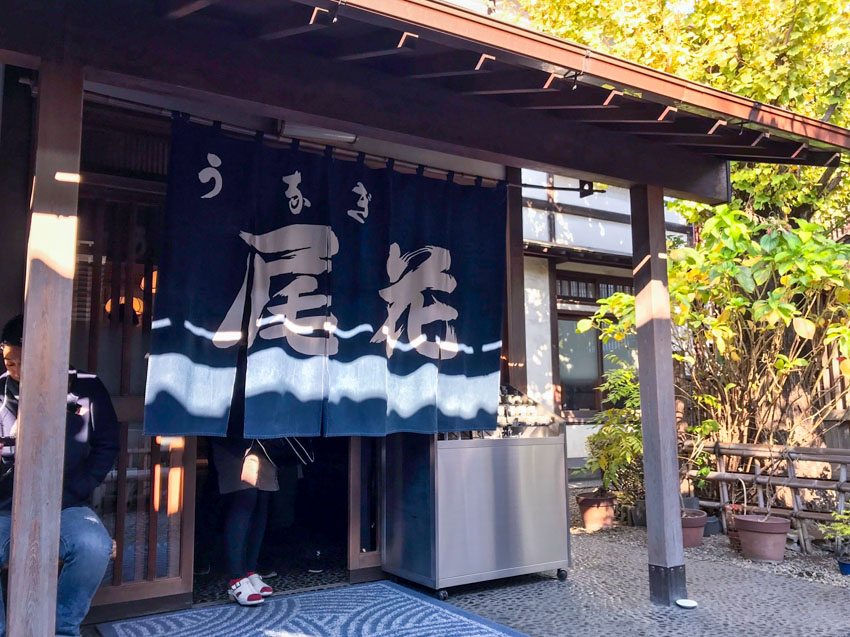 The front of a traditional Japanese resturant, with a short curtain with slits, partially cover ing the entrance. The curtain is navy blue in colour and has Japanese kanji characters on it in white. Someone is standing behind the curtain and their legs and feet can be seen. There is a wooden awning and some green plants in the background.