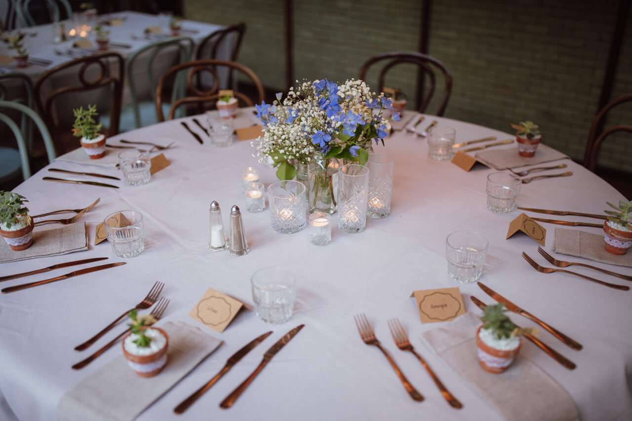 A white round table set up with votives, a floral centrepiece, and cutlery at each seat