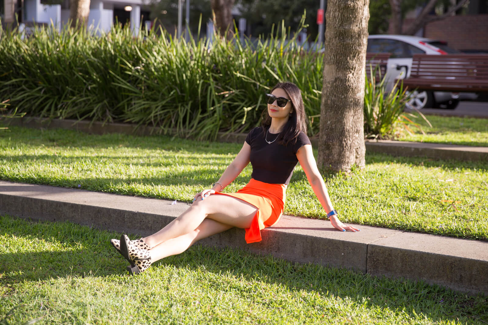 The same woman in previous photos on this page, wearing black square sunglasses on her face. She is wearing a black short sleeved t-shirt and a bright orange skirt. She is sitting on a stone step in a grassy park and has her arm extended behind her and her palm on the ground for support.