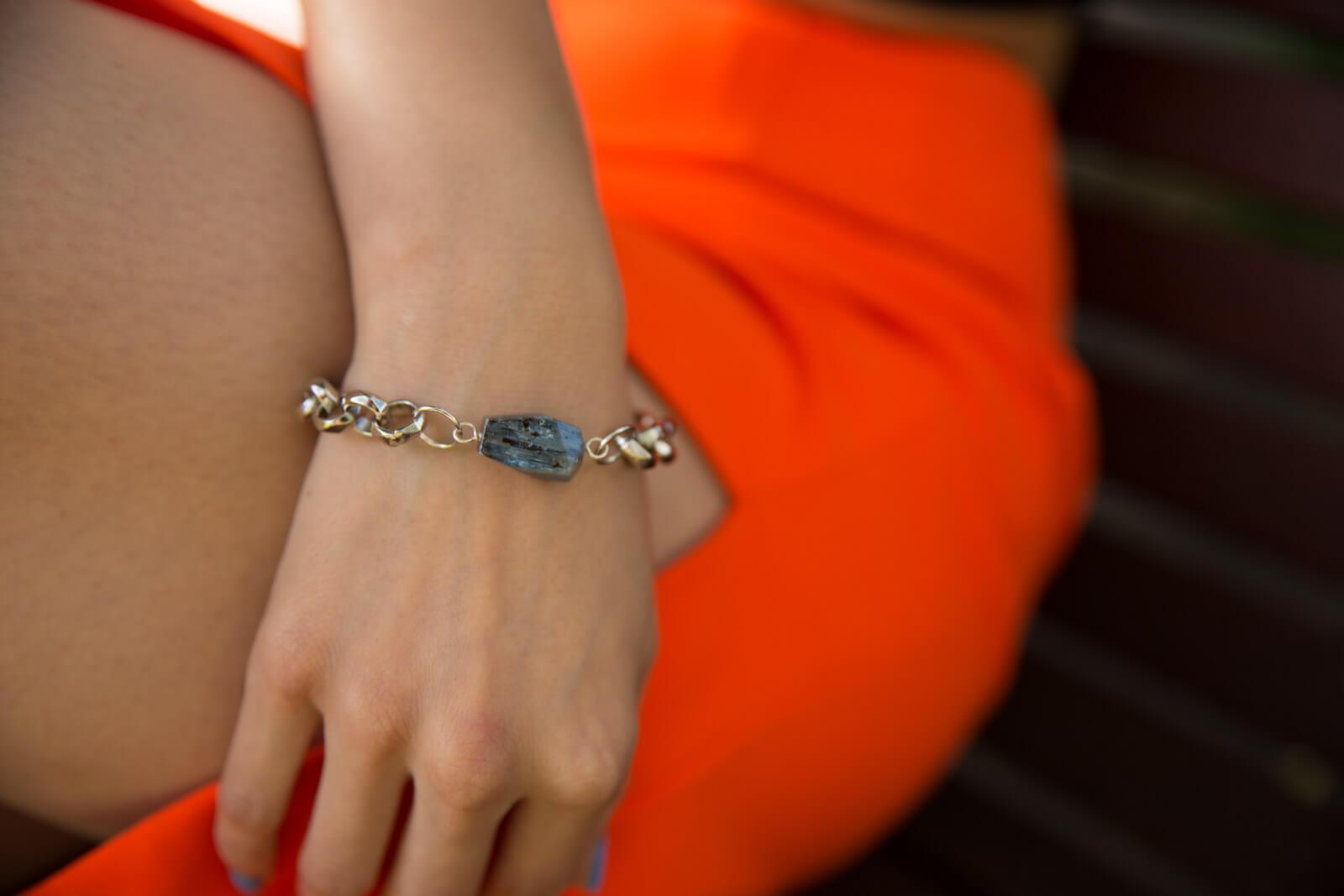 A close shot of a woman's hand against her thigh, wearing a silver chain bracelet with a blue-grey raw stone.