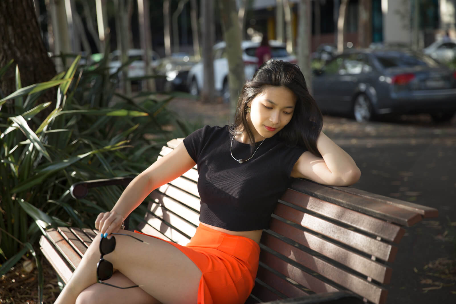 A woman with short dark hair wearing a black short sleeved t-shirt and a bright orange skirt. She is sitting on a wooden bench with one arm resting on the top of the bench, and the other hand holding a pair of black sunglasses. Her gaze is focused downwards.