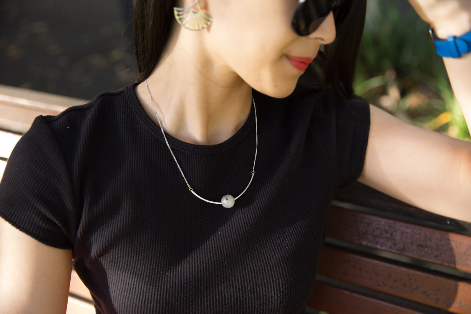A close shot of a woman's neckline; she is wearing a black crew neck shirt and a silver necklace with a white sphere pendant in the centre.