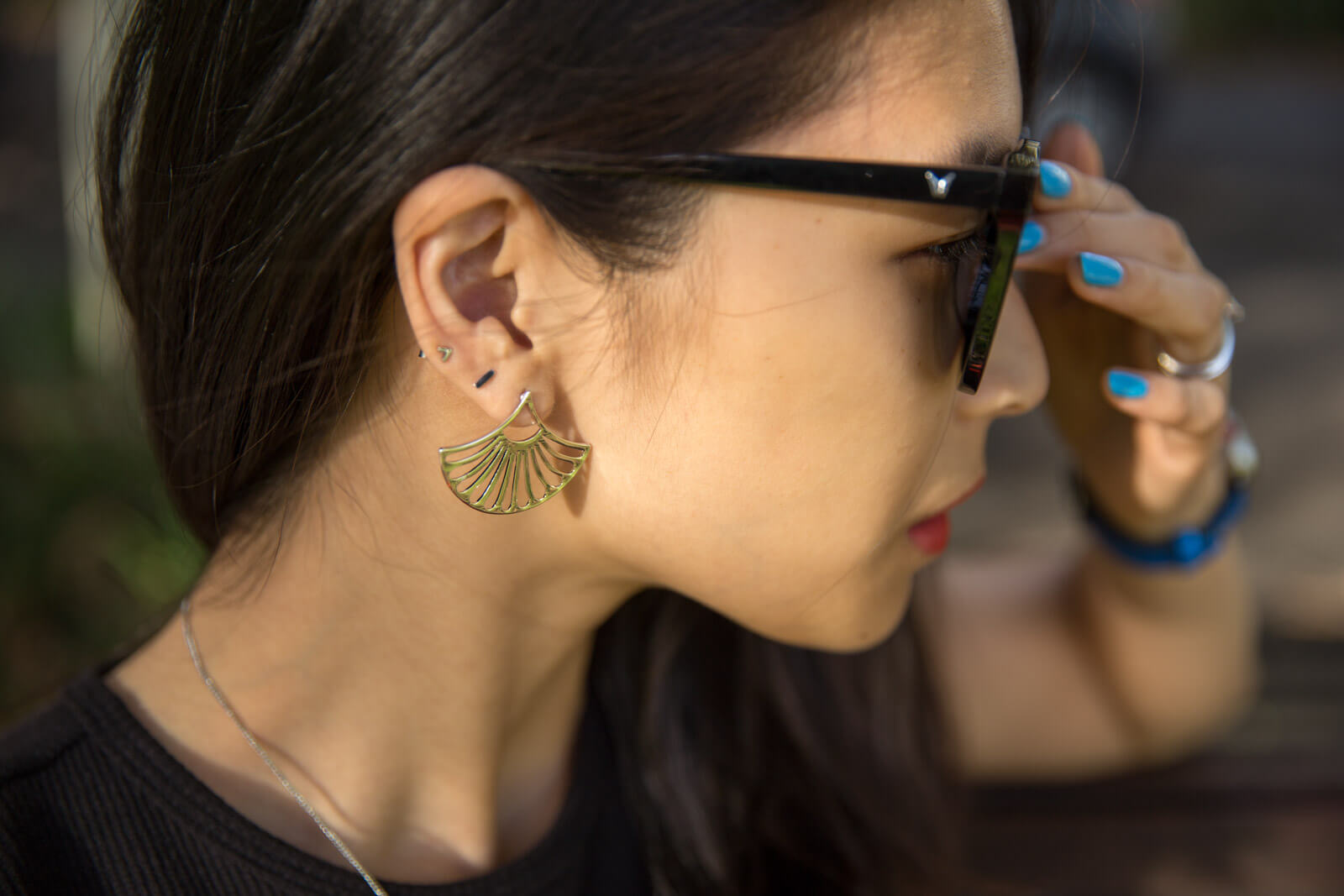 A close up of the side of a woman's face; she has two stud earrings in her ear and a larger palm/fan shaped earring on the bottom lobe. She has light blue painted nails and is pushing her glasses at the nose bridge.
