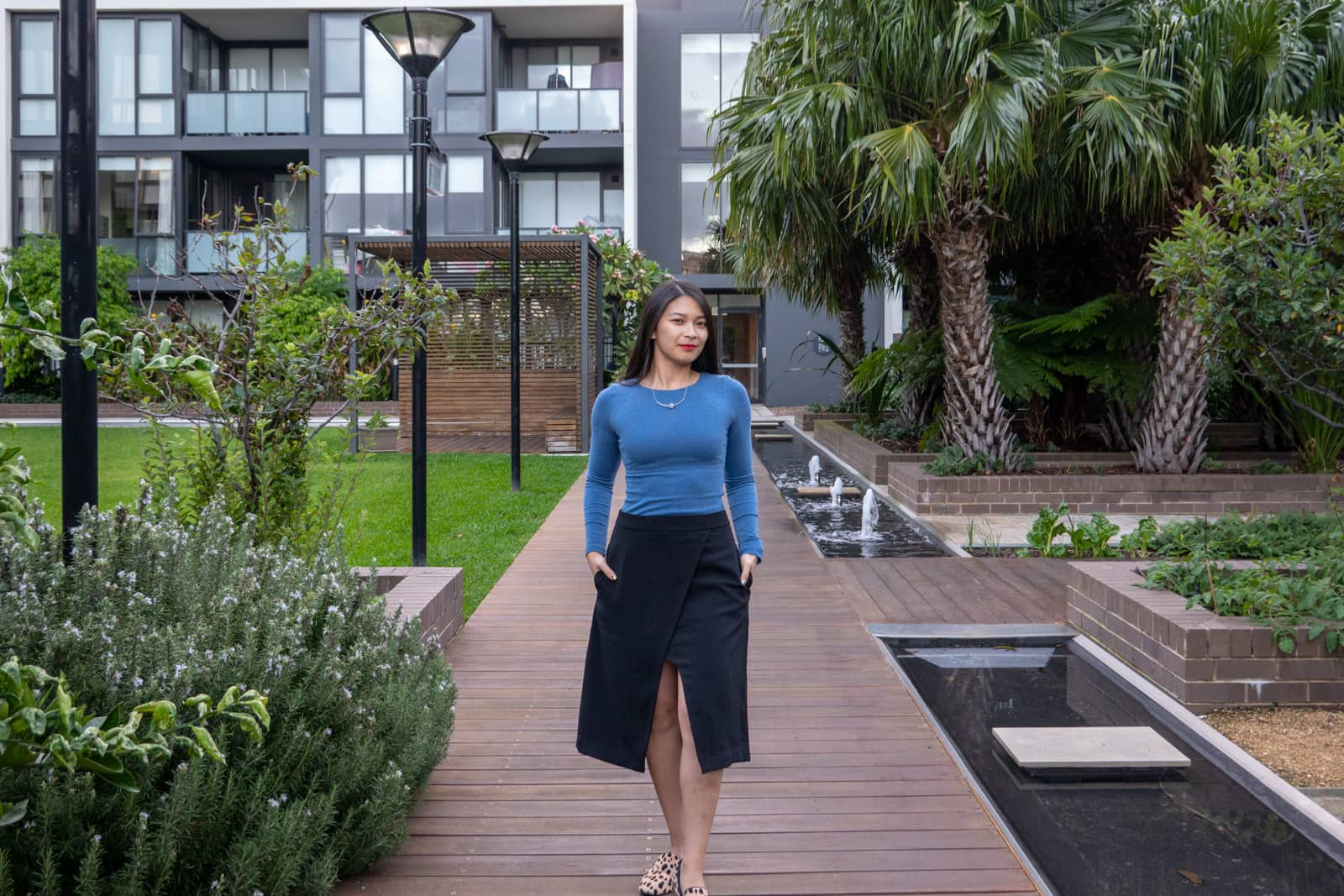 The same woman in other photos on this page, wearing the same outfit. She is standing facing the camera and has her hands in her skirt pockets. She's standing on a wooden pathway with brick-bordered gardens in the background, and an apartment building with frosted glass balconies