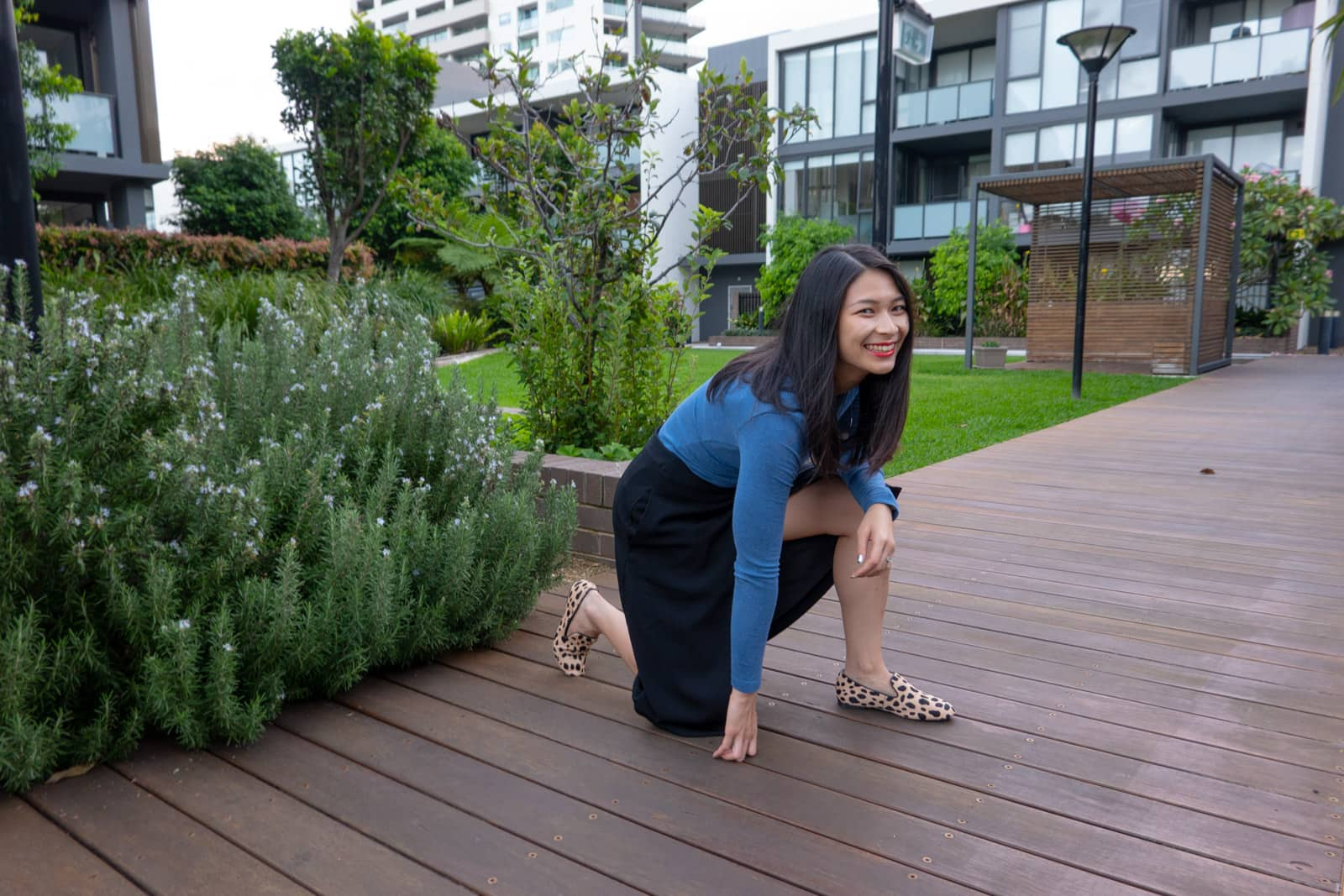 The same woman in other photos in this post, but posing on a wooden plank path with one knee on the ground and the other leg propped up. She is grinning, mid-laugh. In the background a cabana and a block of apartments can be seen