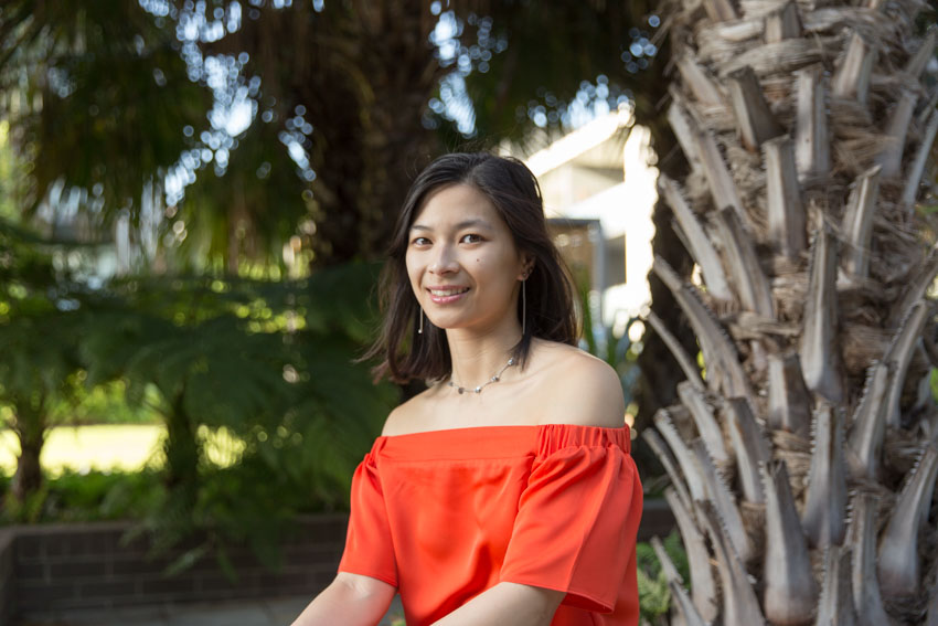 A girl with an orange top, smiling. Trees are in the background.