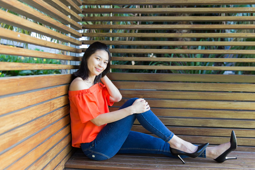A girl sitting in a wooden cabana sideways with one leg outstretched and one knee bent, smiling. She is wearing an orange top, dark blue jeggings, and black high heels. Her left hand is held behind her head and the other hand on her raised knee.