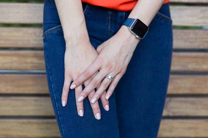A girl's left hand on top of her right hand, resting on her thigh as she is standing. She is wearing silver diamond rings on her left ring finger and a smartwatch with a blue band.