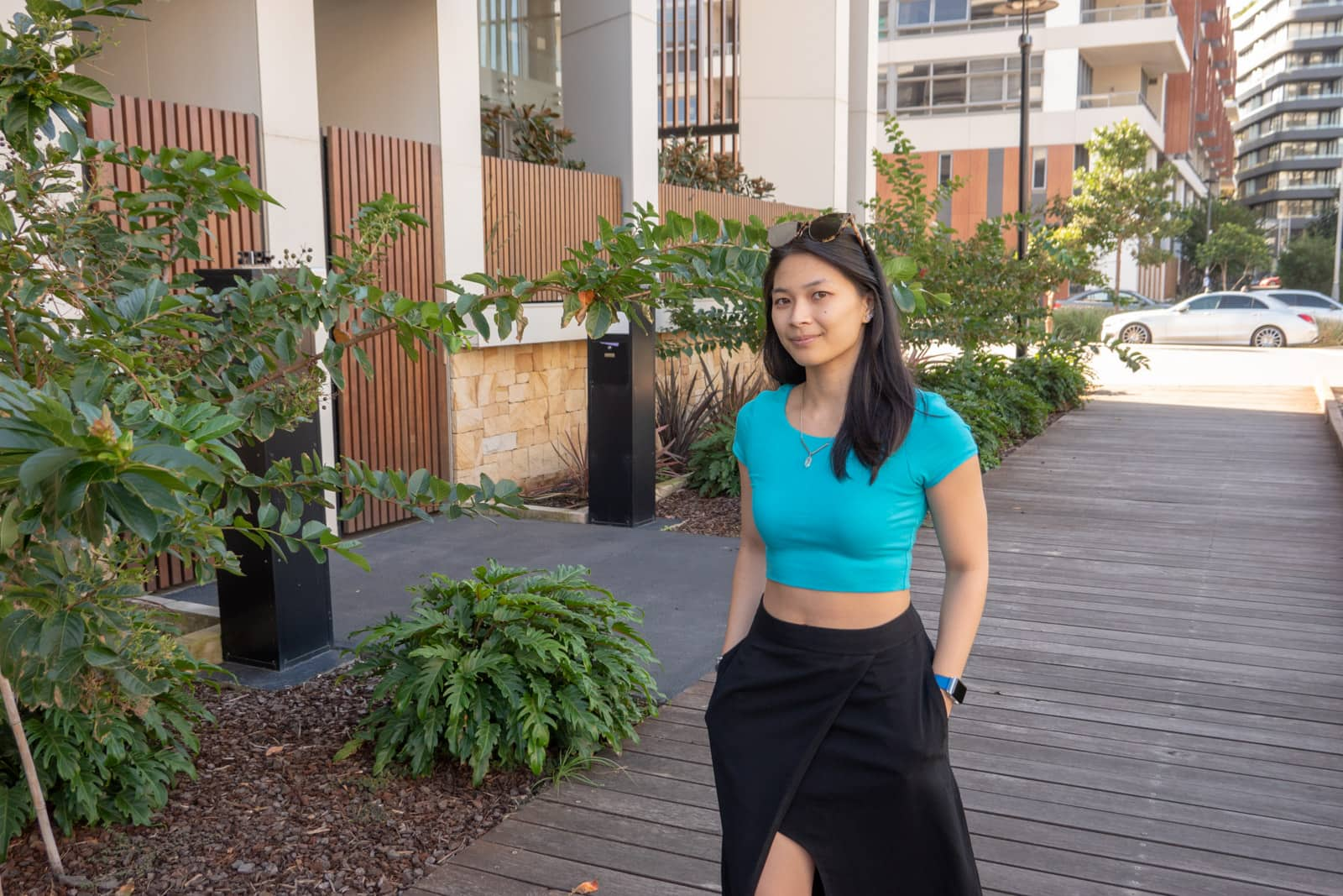The same woman in other photos on this page, wearing the same outfit. She has her hands in her pockets and is standing on a wooden path. There are apartment buildings in the background