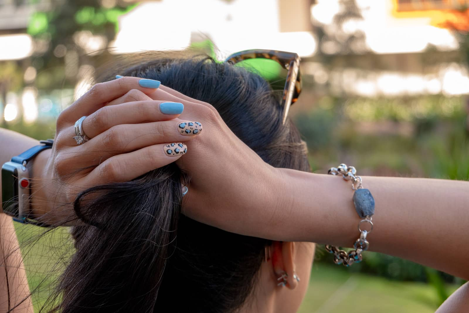 A close-up view of a woman's head from behind. Her hands are holding her dark hair up in a ponytail. She has blue nails with a few nails having leopard-print nail art on them