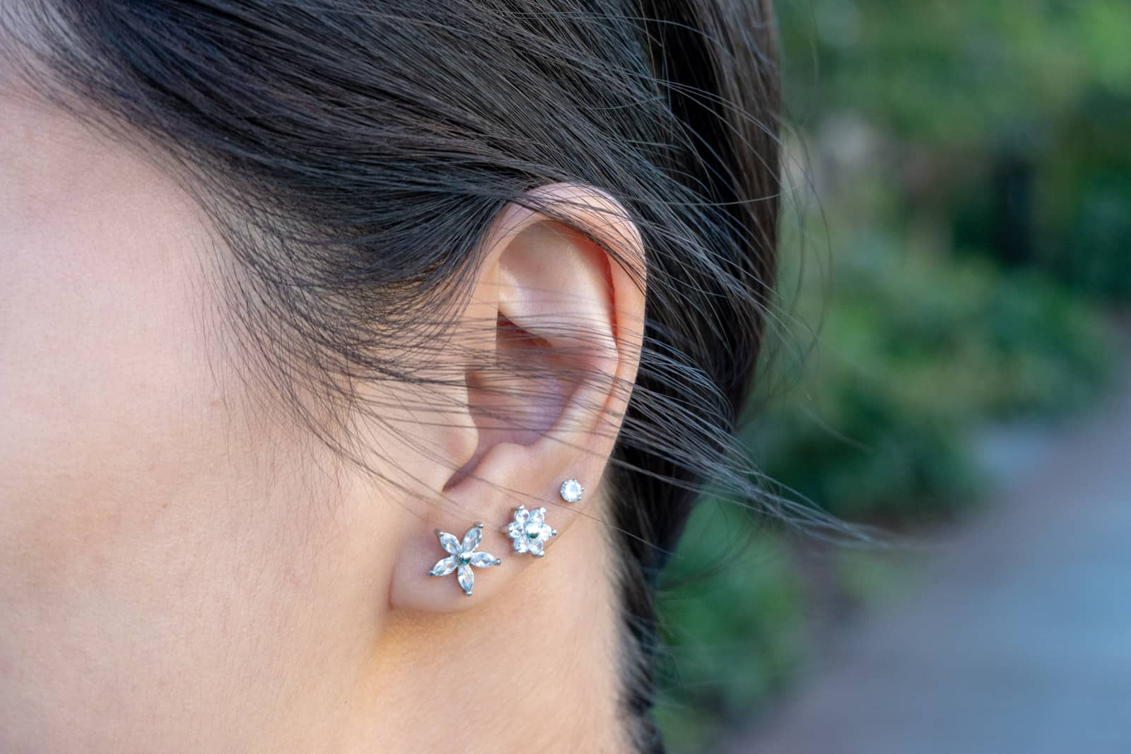 A close-up of a woman's ear with three cubic zirconia studs studs in the lobe. Two of the studs resemble flowers and the other is a simple stud