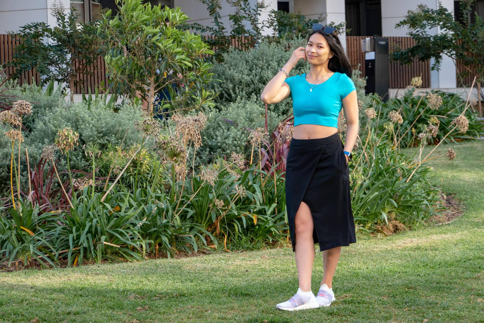 A woman with short dark hair, brushing some hair behind her ear. She is wearing a turquoise top and a long black skirt with white running shoes. She's standing in a garden