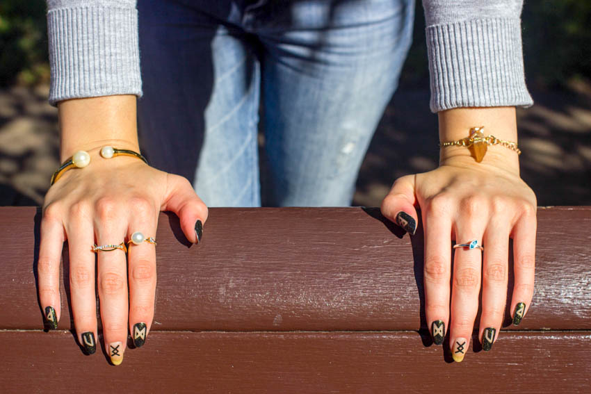 Close up of my hands on a bench, showing my nail art and rings
