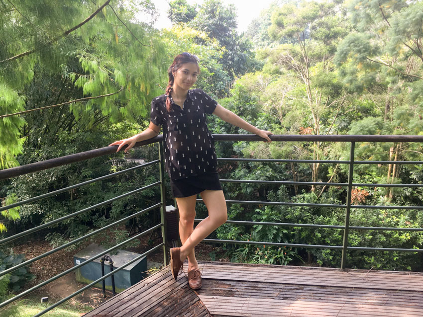 Me leaning in the corner of a wooden walkway above ground