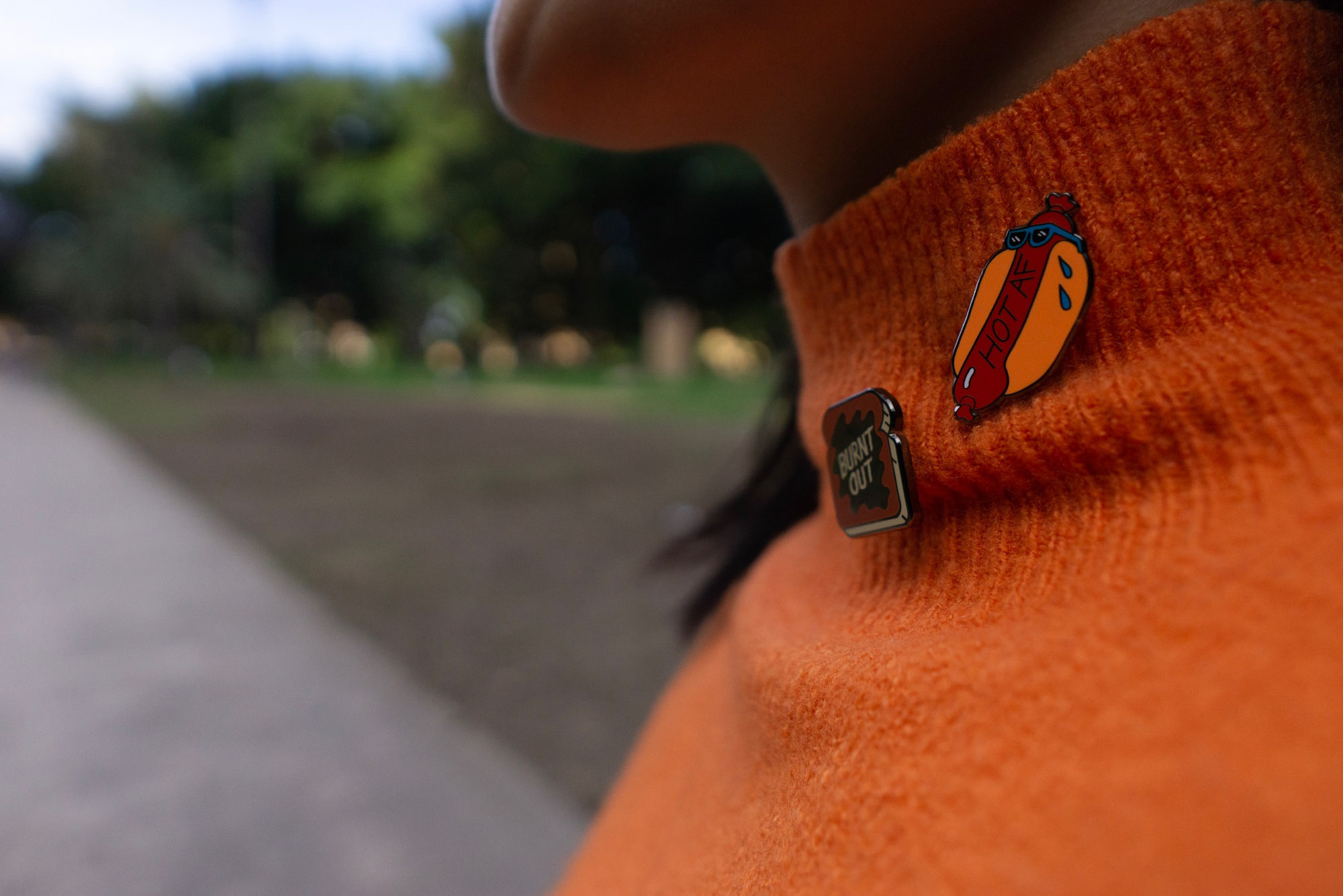 "A close up of an orange turtleneck sweater worn by a woman. She is wearing two pins on her sweater; one a hot dog with the text ""HOT AF� and the other a piece of toast reading ""Burnt out�"