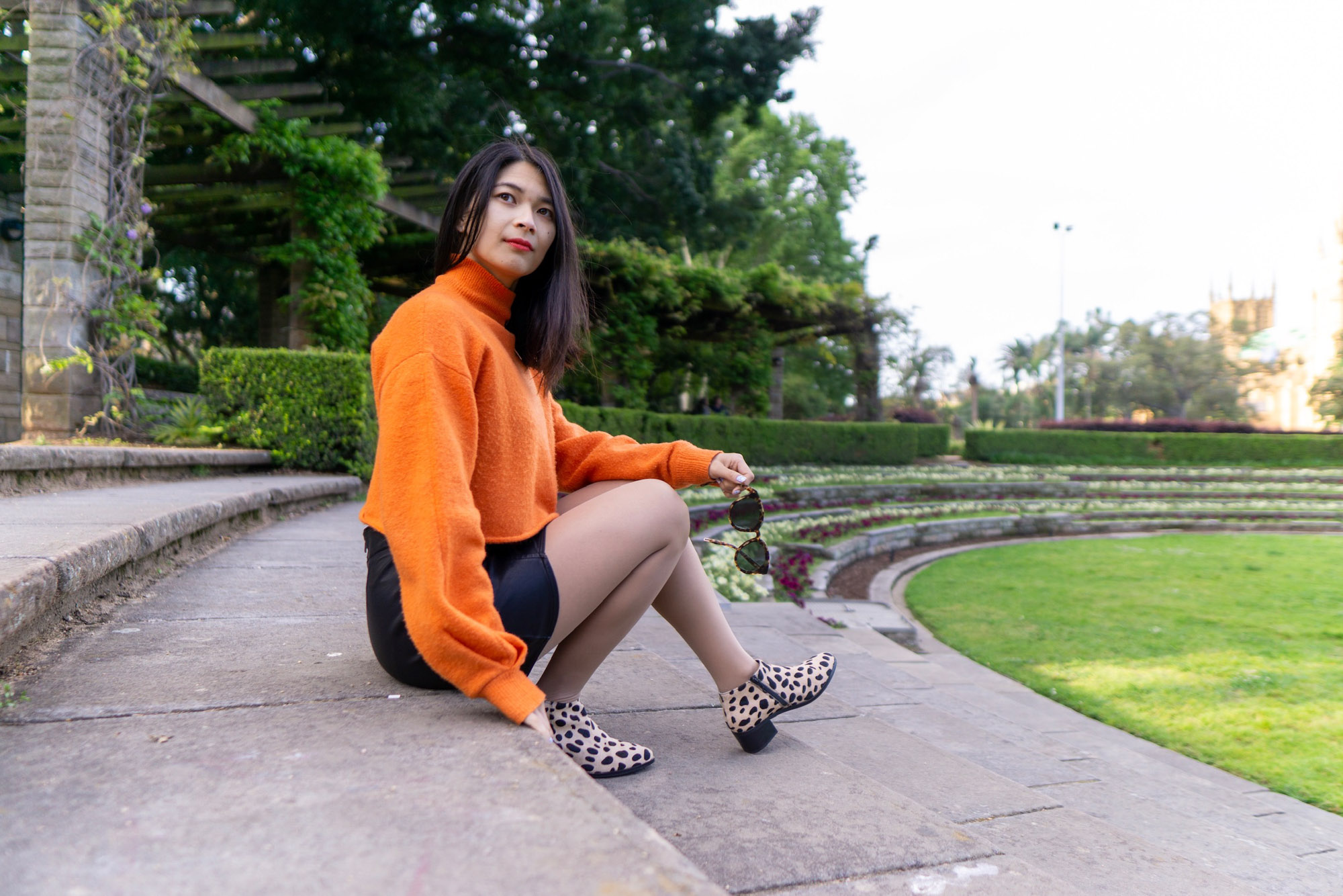 A woman sitting on stone steps. She is wearing a bright orange sweater and a black skirt. Her shoes are light in colour with black spots, resembling giraffe print. She is looking away from the camera and holding a pair of sunglasses in her left hand