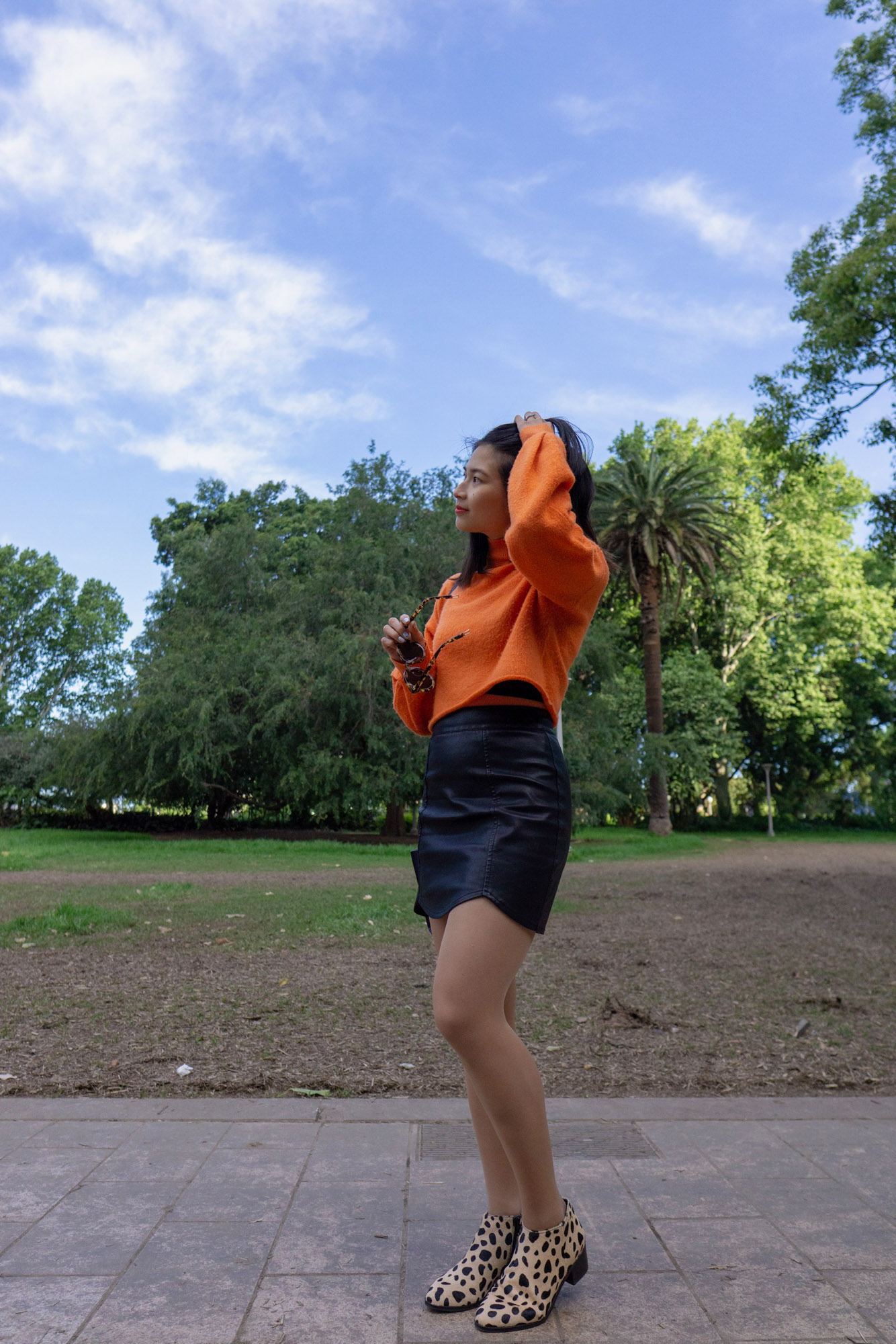 A woman with short dark hair, standing in a park during the day. She is wearing a bright orange sweater and a black skirt. Her boots have black spots resembling a giraffe print