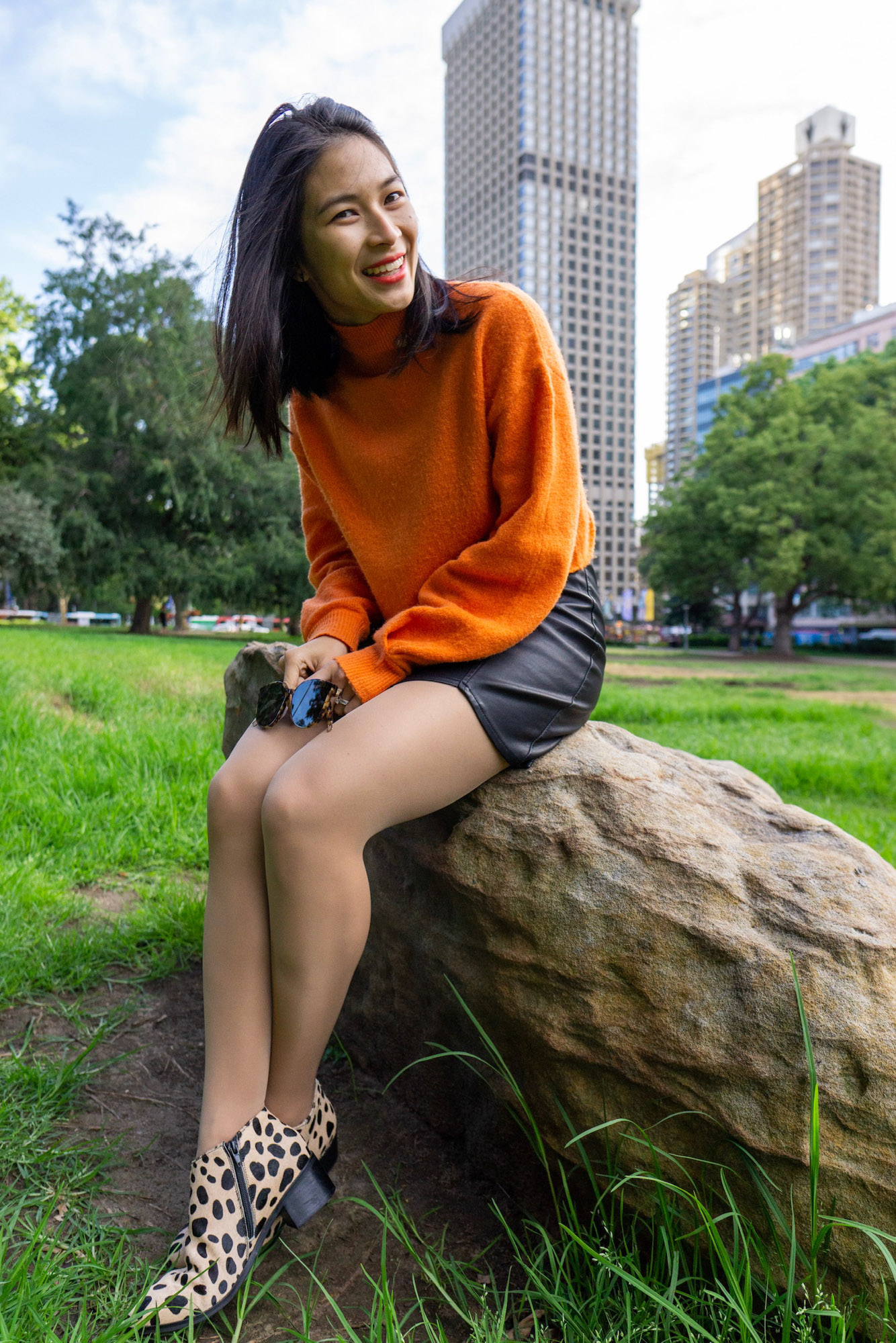 A woman with short dark hair, sitting on a large rock. She is wearing a bright orange sweater and a black skirt. She is in a park and there are skyscrapers behind her.