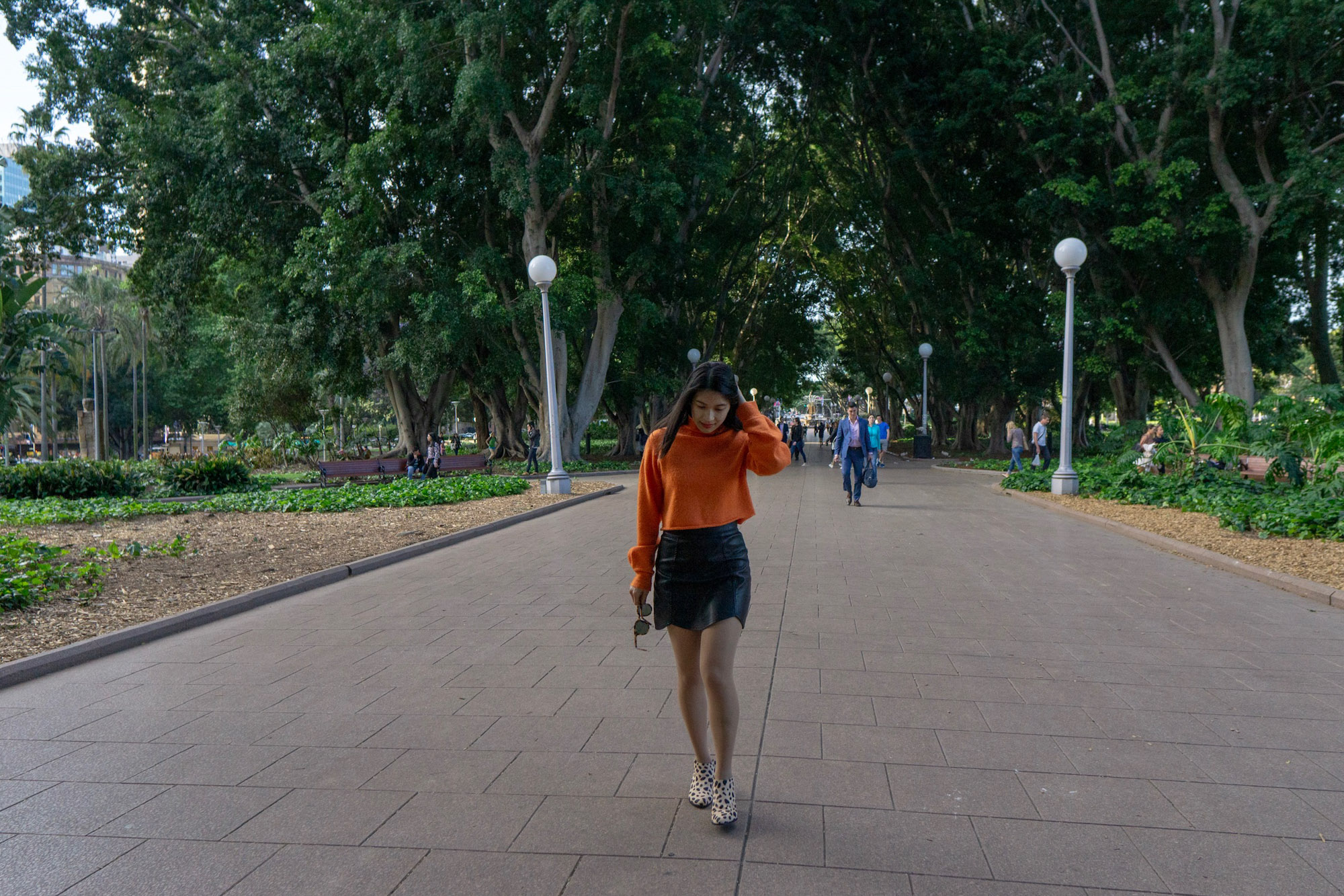 A woman with short dark hair, walking down a pathway in a park with lots of green trees. She is wearing a bright orange sweater and a black skirt.