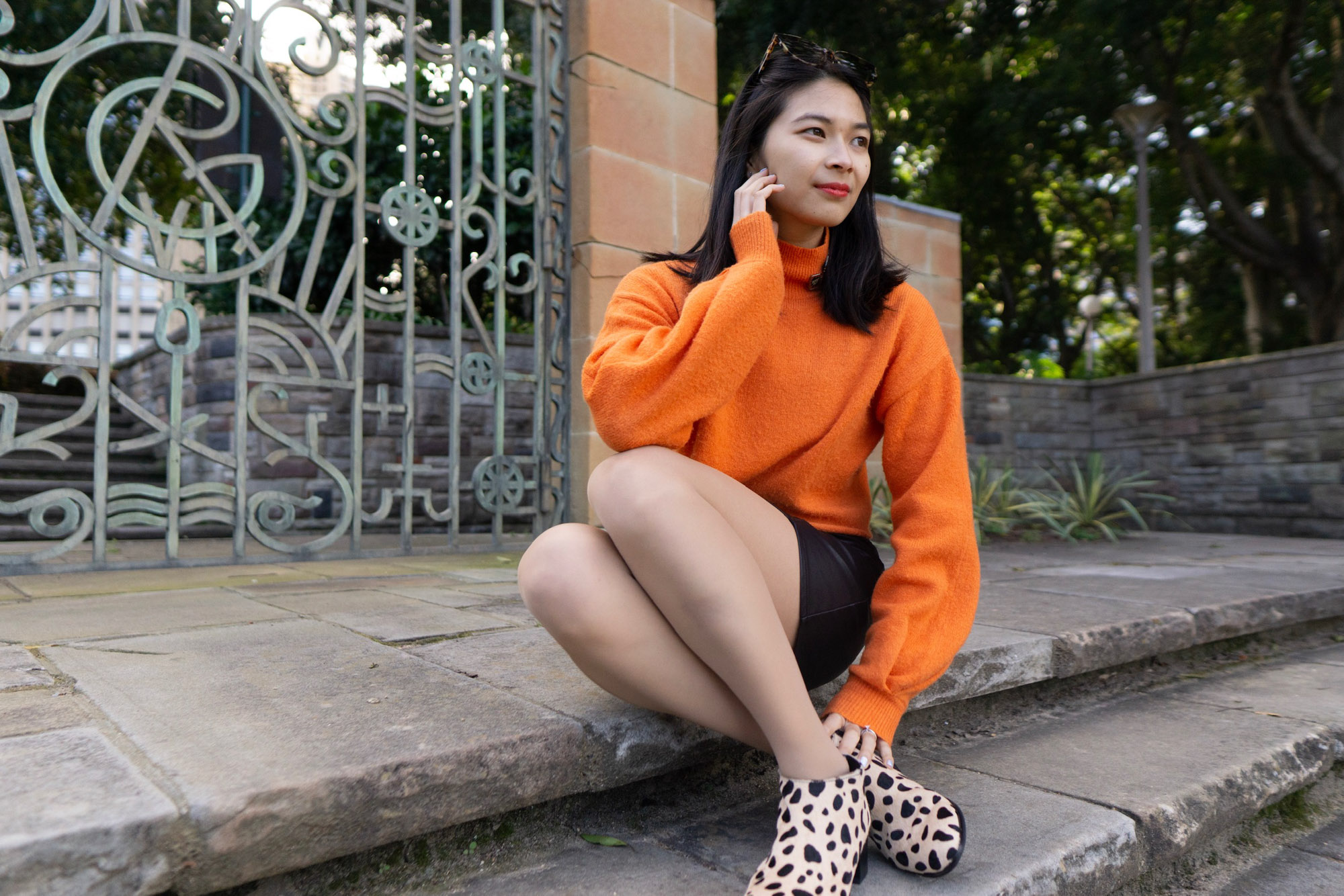 A woman sitting on stone steps. She is wearing a bright orange sweater and a black skirt. Her shoes are light in colour with black spots, resembling giraffe print. Behind her is a metal gate in a pattern.