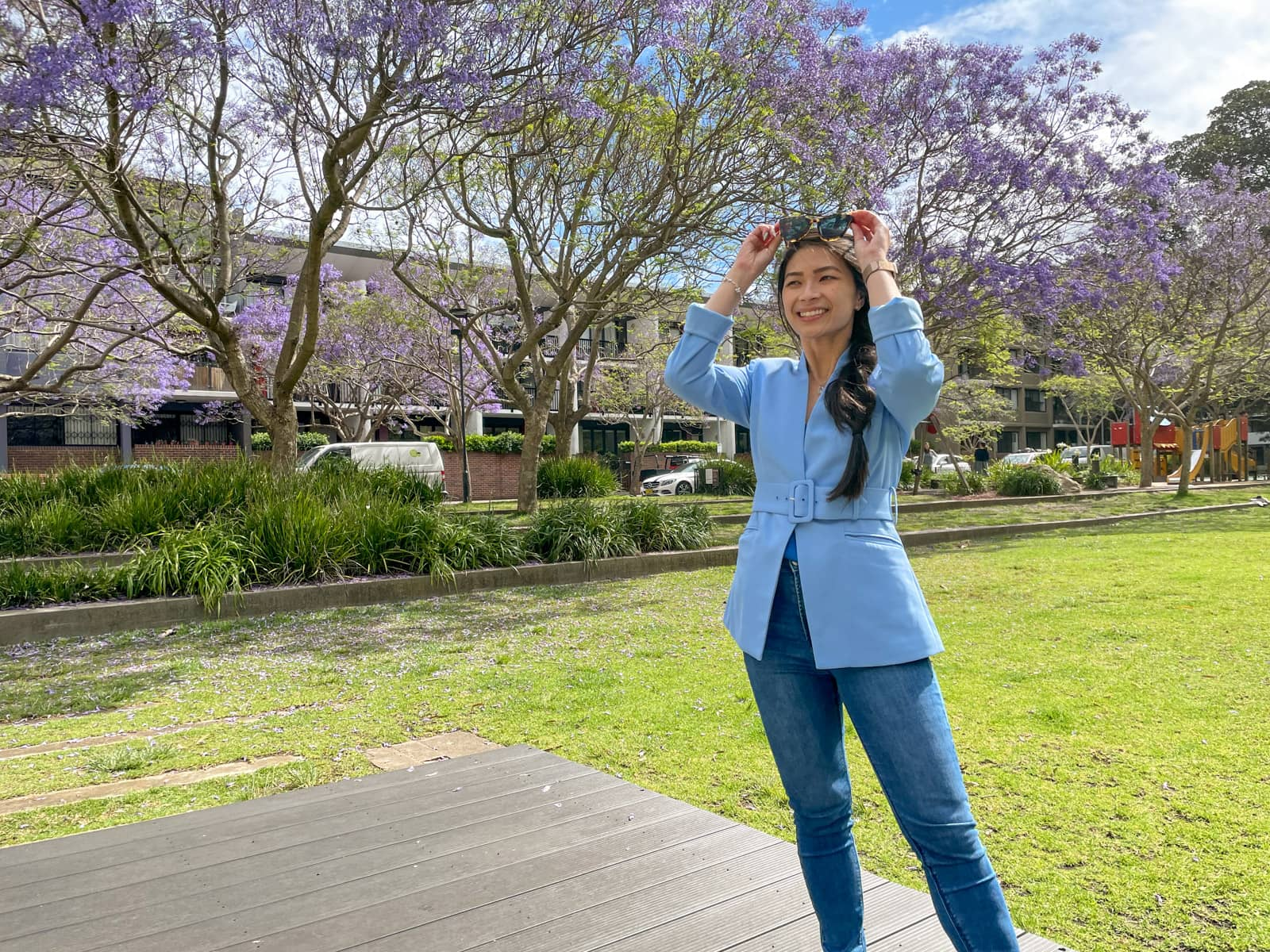 A woman with fair skin and long dark hair braided loosely in a side braid. She is wearing a light blue blazer and blue jeans and is holding her sunglasses on top of her head. She is grinning. In the background are jacaranda trees in a park