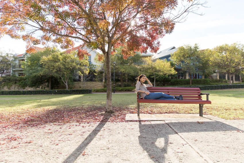 Me sitting sideways on a park bench with a tree shedding autumn-coloured leaves