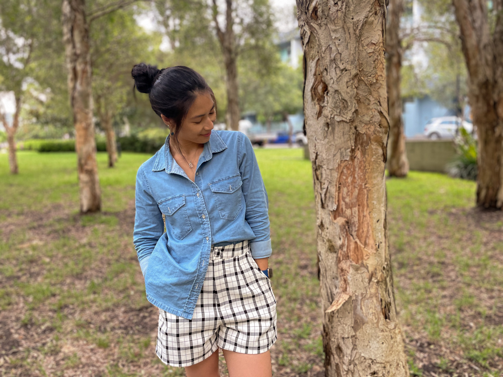 A woman wearing a chambray button-up shirt, half tucked into a pair of shorts with a black and white check pattern. She has her hands in her pockets. Her dark hair is up in a bun and she is looking down and to the side, not facing the camera. She is standing amongst a handful of trees spaced apart.