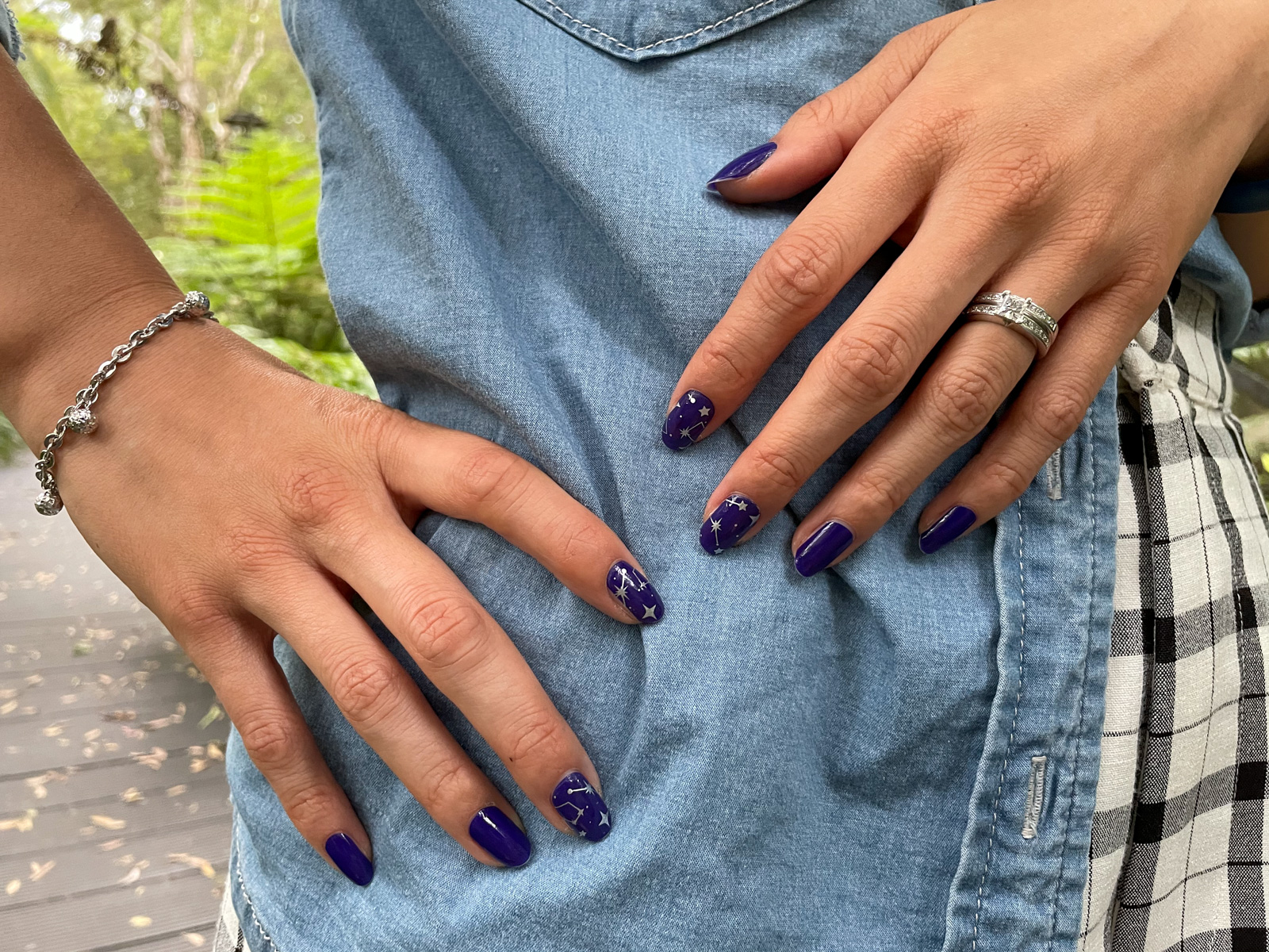 A close-up of a woman's fingernails, with dark blue nail wraps applied. Some of the nails have a silver starry pattern on them.