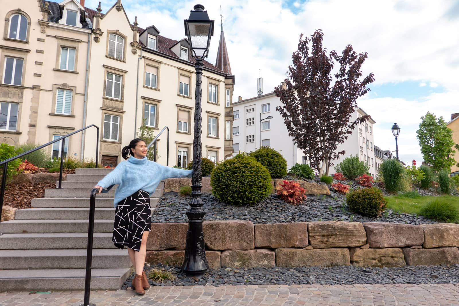 A woman in a blue sweater and a black and white patterned skirt, next to a set of stairs. She's holding onto a lamppost and in the background is a nice garden and some old buildings with tall windows