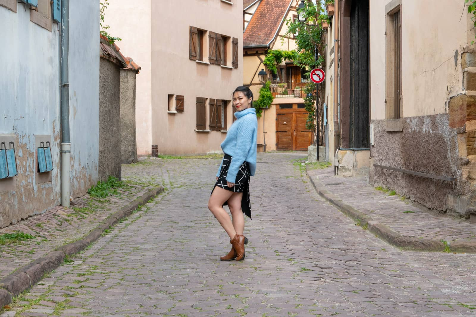The same woman in other photos on this page, dressed in the same clothes. She is standing side-on, leaning back into her hip with one knee bent. She is in the middle of a quiet cobblestone road.