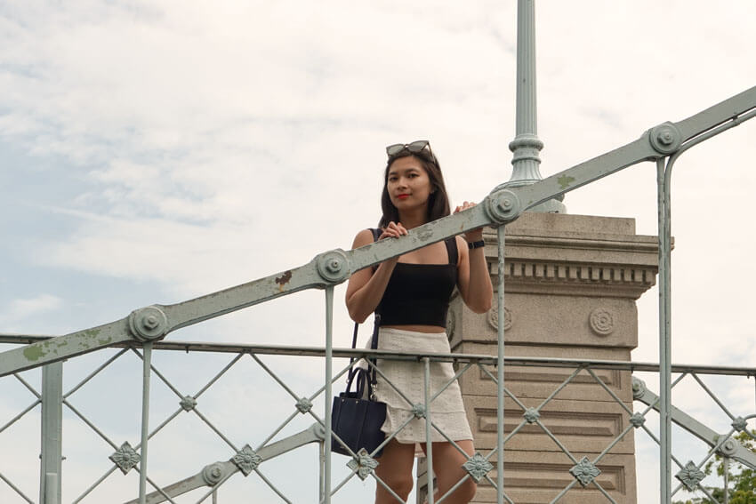 The same woman from the previous photo, standing on a bridge, with her hands resting on the railing.
