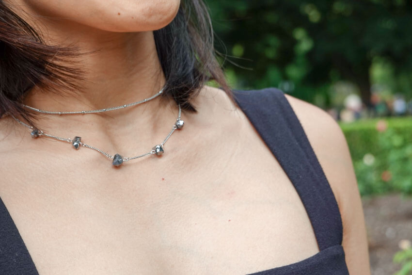 Close shot of a woman's neckline, wearing two choker necklaces, one spaced with small silver rocks