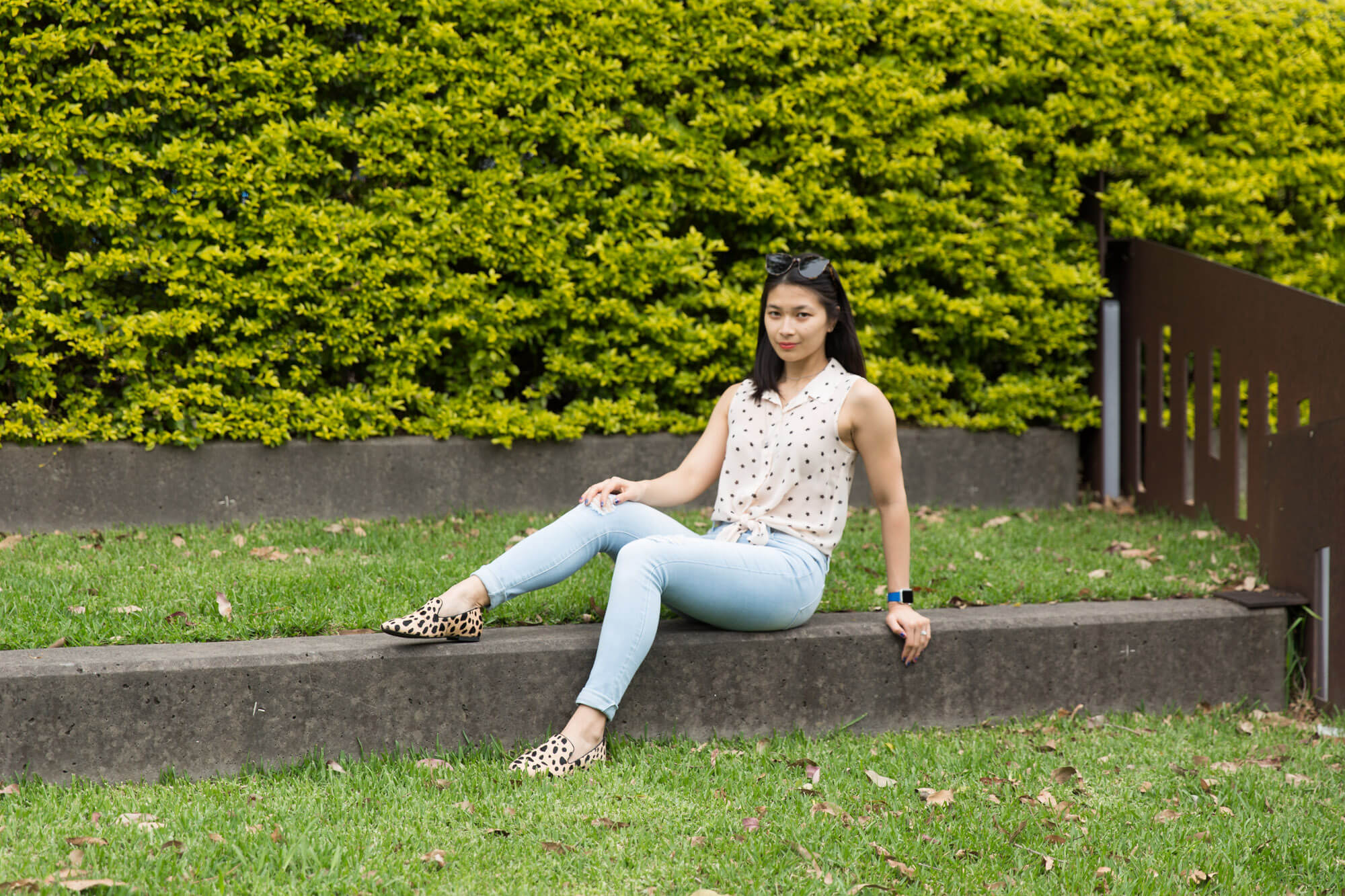 A woman sitting on the concrete step of a grassy park. Her legs are bent and slightly outstretched and she is leaning back using one of her hands as support. She is wearing light blue jeans, a light coloured top and shoes, which have patterns on them. She has sunglasses on top of her head