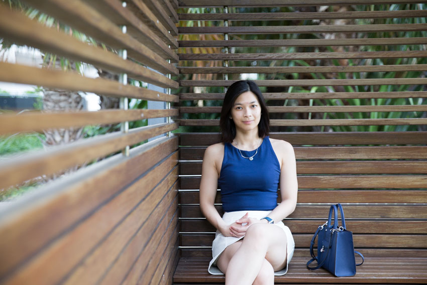 A woman with short dark hair sitting in a cabana facing the camera. She is wearing a blue sleeveless top and has a small square-shaped blue bag next to her.