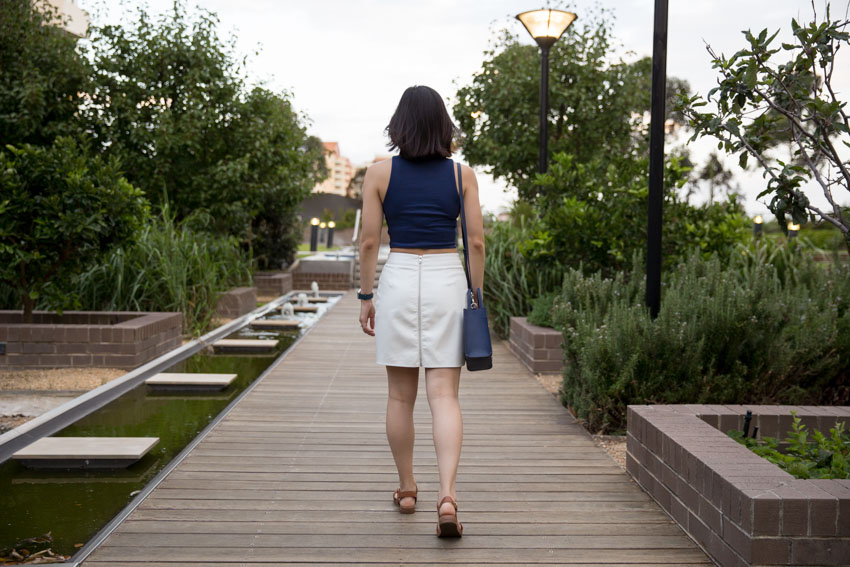 A girl walking on a path of wooden slats, wearing a white skirt that zips all the way up the back. She has short dark hair and is carrying a small navy handbag off her shoulder.