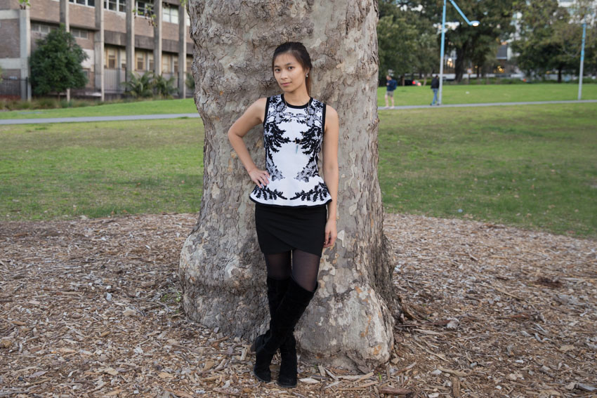 Full body shot in front of a tree trunk with one hand on my hip, one foot crossed in front of the other