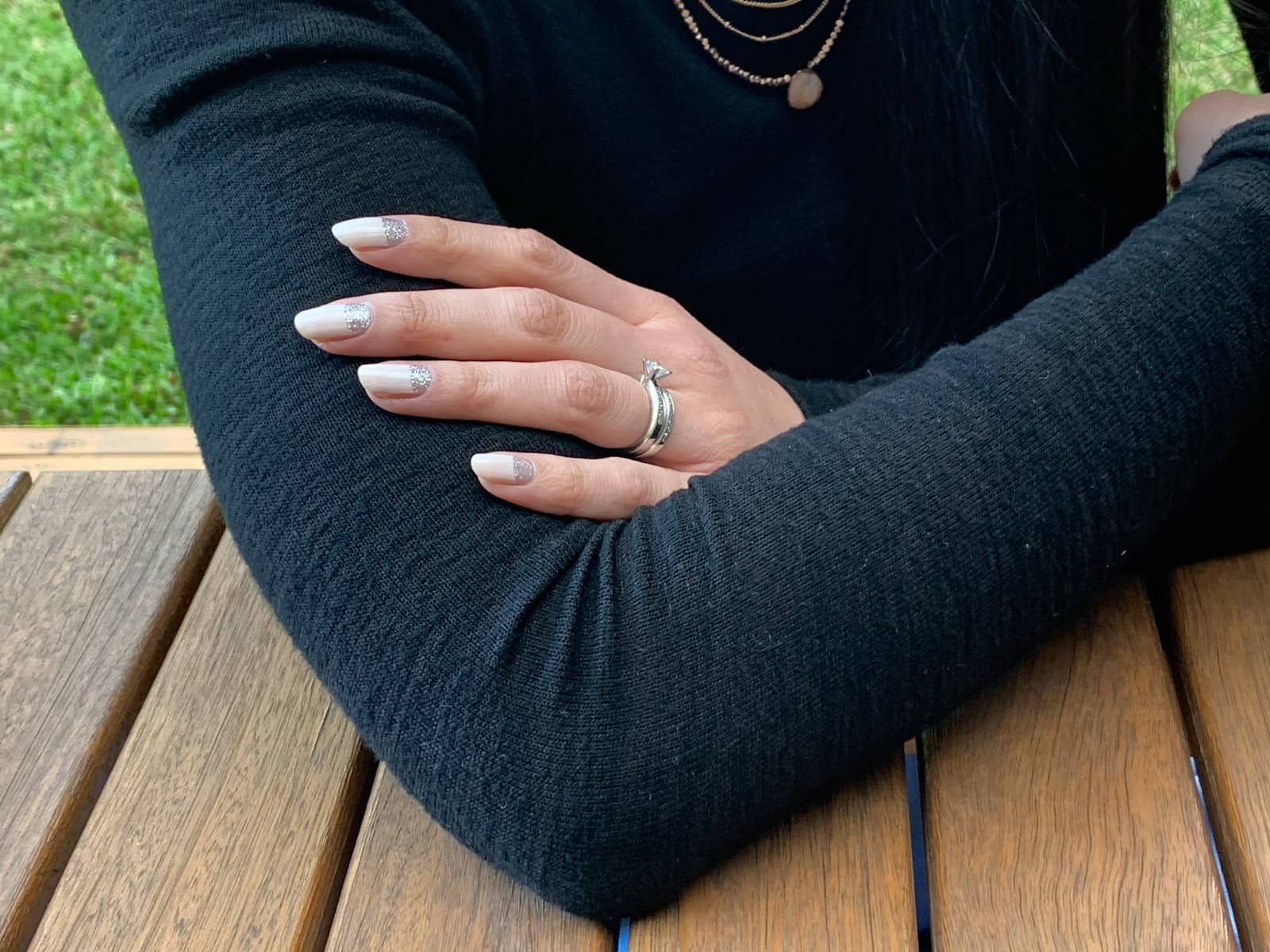 A close-up of a woman's arms, folded. She has nail art on her fingernails – silver glitter near the cuticles, and the remainder a light beige colour. She is wearing a silver wedding and engagement ring on her fourth finger.