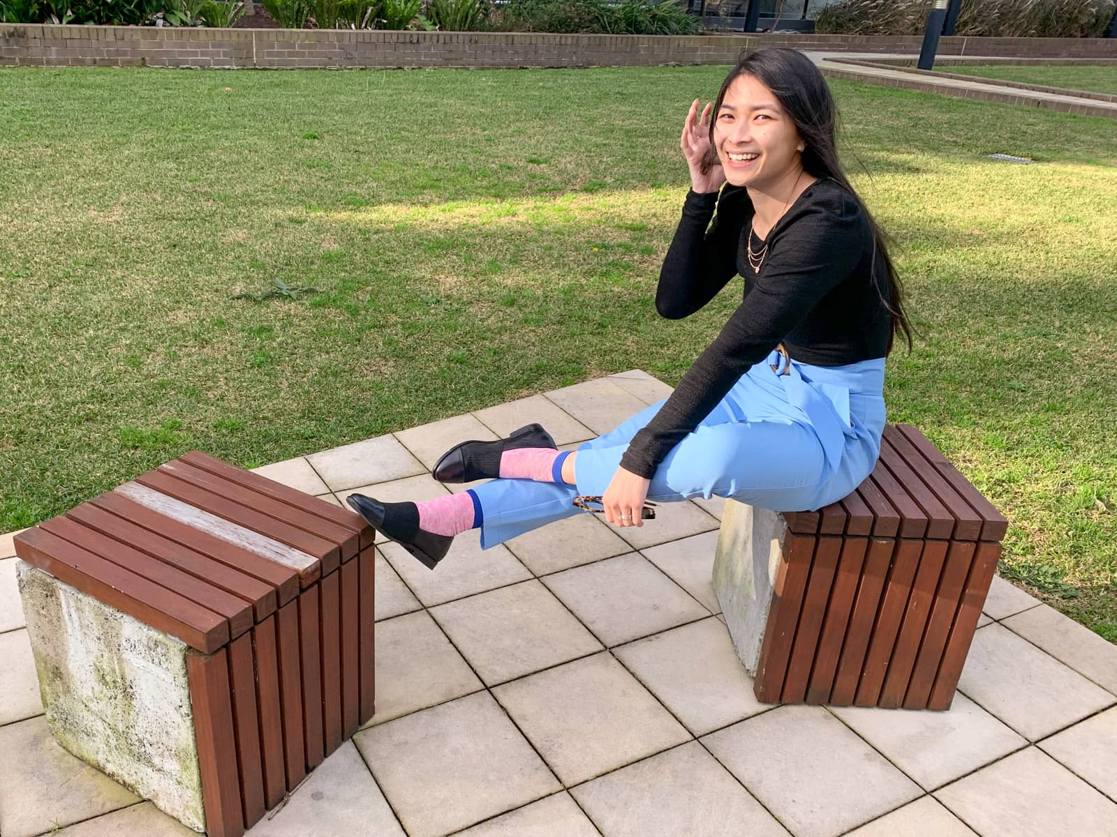 A woman sitting on a concrete cube-shaped block topped with wooden planks, made to function as a stool. She has her feet propped up on another wooden block. She is wearing a black long-sleeved top and sky blue pants, and is smiling and tucking hair behind her ear.
