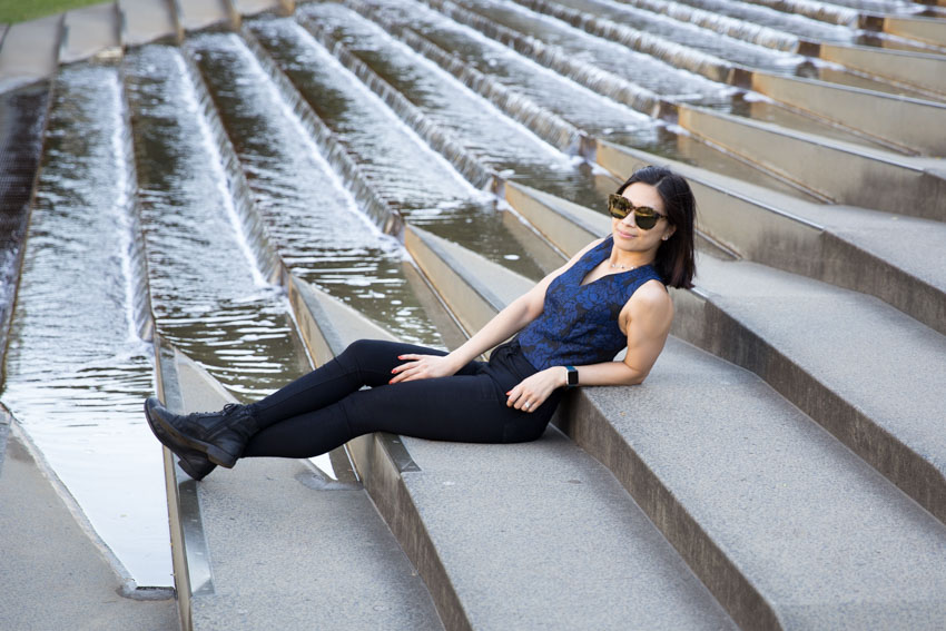 Me sitting on concrete steps next to a water feature, leaning back with my sunglasses on