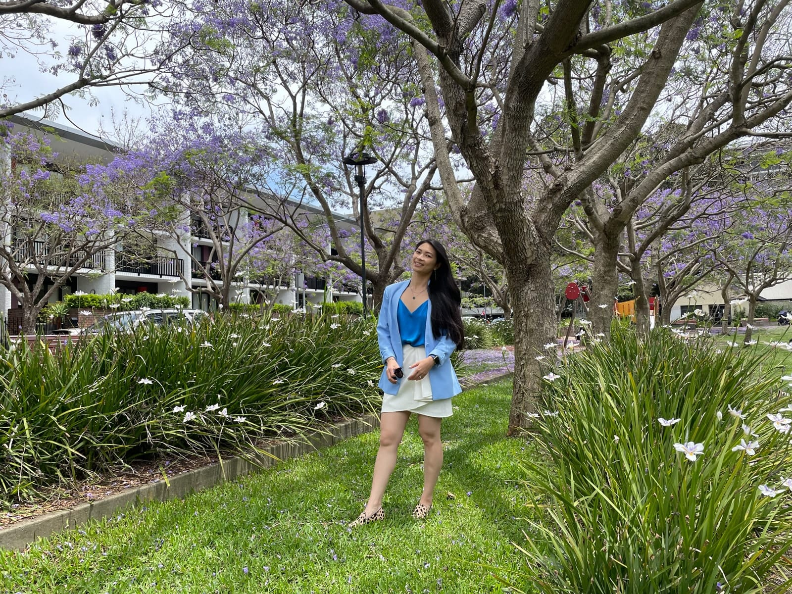 A woman with long dark hair, wearing a blue blazer over a blue top and white skirt, standing in a lush green park with jacaranda trees. She has loafers with a giraffe animal print