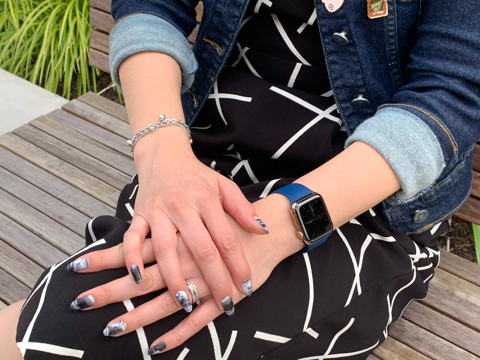 A close-up of a woman's hands, crossed over each other, on her knee. The woman's fingernails have black and white swirly nail art. She is wearing a blue watch on one wrist and a couple of bracelets on the other. She is wearing a black jumpsuit with white geometric lines on it.