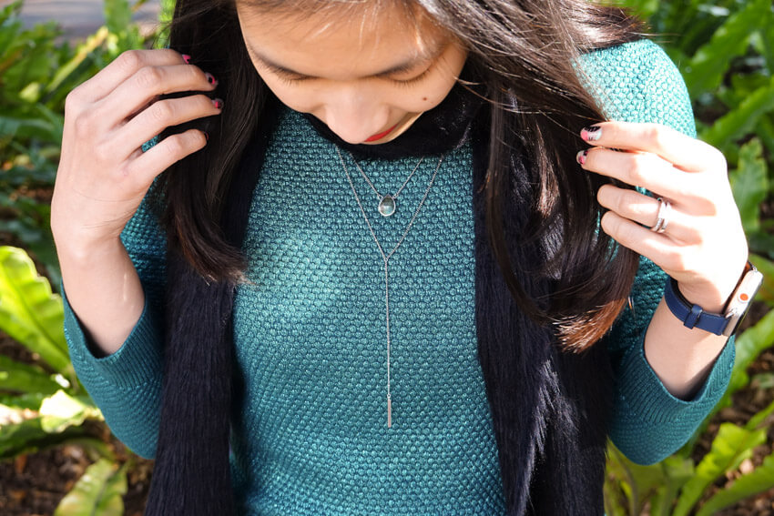 The same woman from the previous photo, wearing the same clothes. This is a closeup of her lariat necklace. Her hands hold her hair away from her chest area and she is looking down.