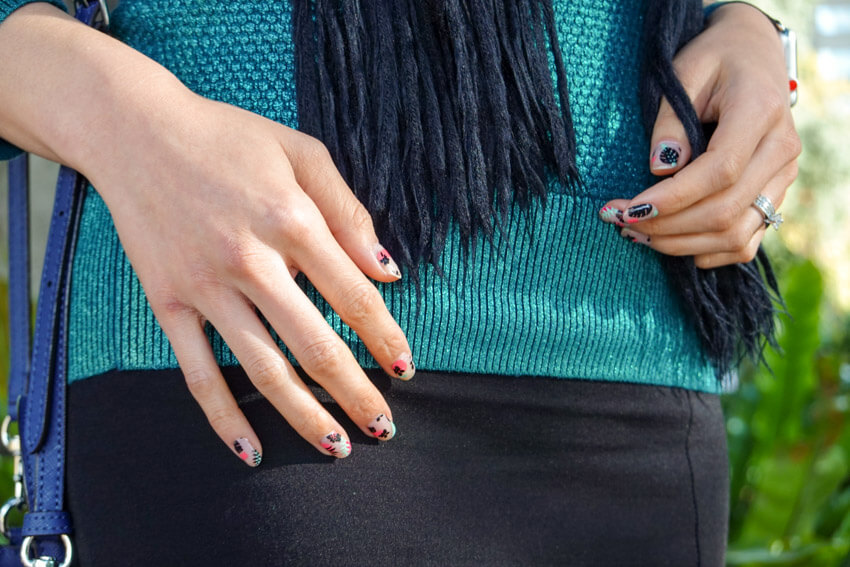 Close up of a woman's hand with pink, black and light green nail art. She's wearing a green top and a black skirt.