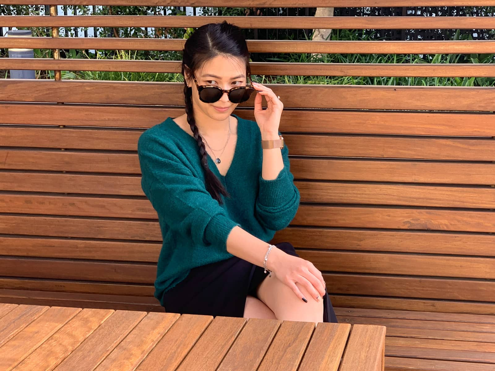 A woman with long dark hair, wearing a green sweater and black skirt, sitting in a wooden cabana, behind a wooden table. She has a braid over one of her shoulders. One of her hands rests on her knee, which is crossed over the other. Her other hand is raised to her sunglasses which are partially obscuring her face